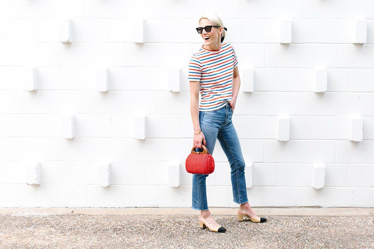 Девушка в синих джинсах, футболка в полоску и красная сумочка