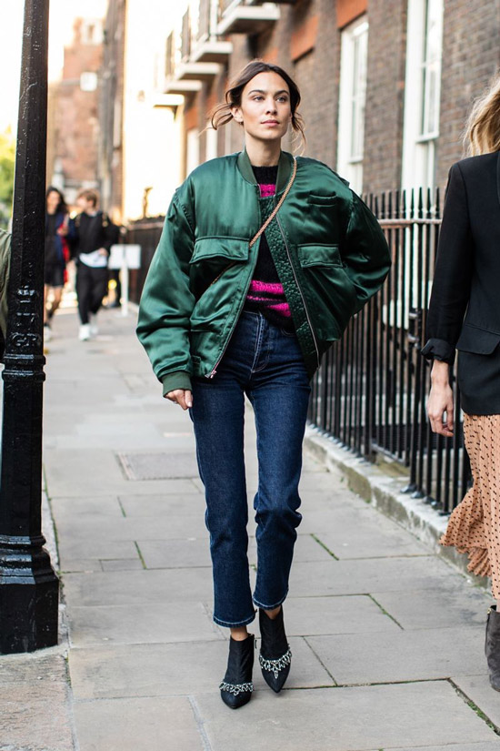 Девушка в синих джинсах, зеленый бомбер и ботильоны на шпильке