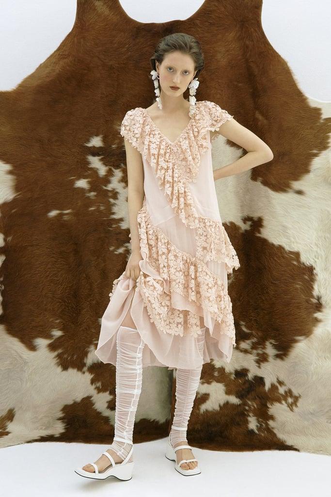 Девушка в светло-розовом платье с кружевами и рюшами, белые босоножки