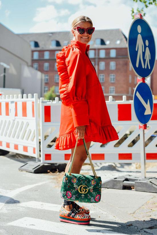 Девушка в свободном красном платье, сандалии на платформе и зеленая сумка
