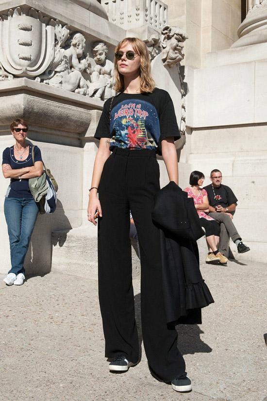 Девушка в свободных черных брюках, футболка с принтом и кеды