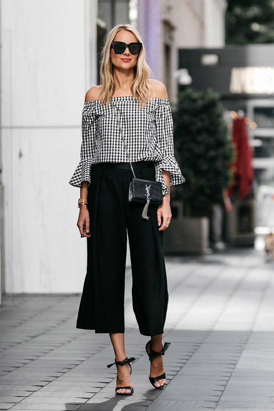 Девушка в свободных укороченных брюках, блузка в клетку и босоножки на каблуке
