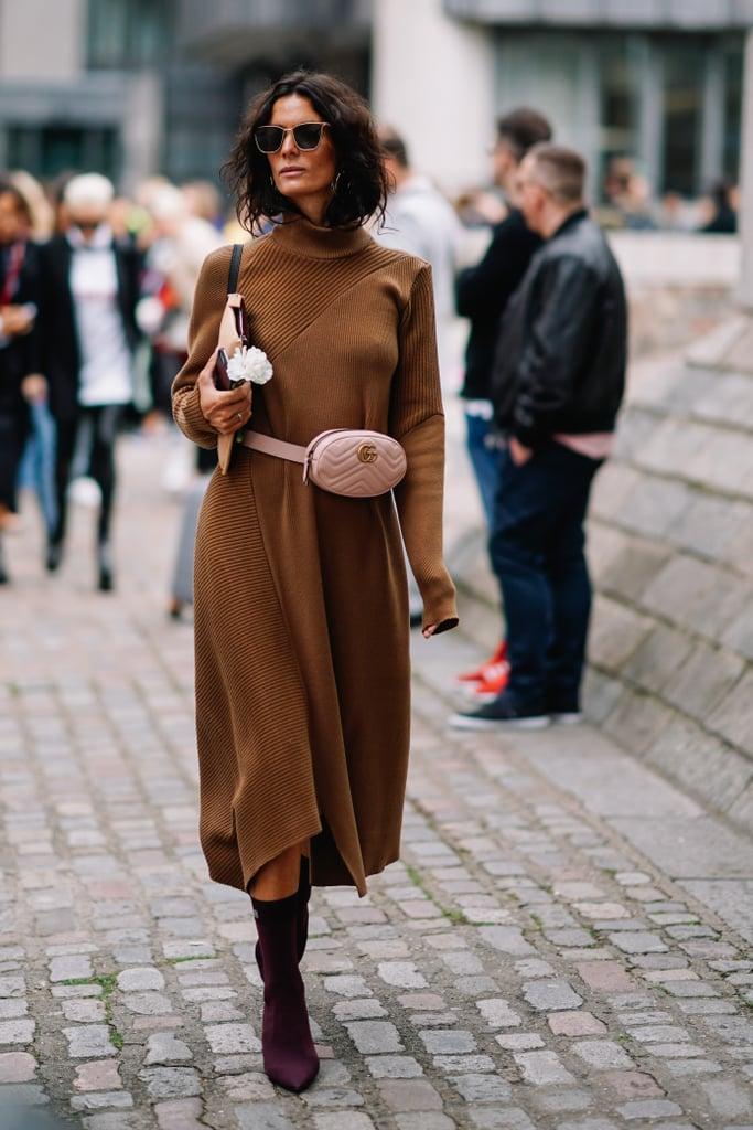 Девушка в теплом коричневом пальто миди, фиолетовые ботильоны и розовая поясная сумка