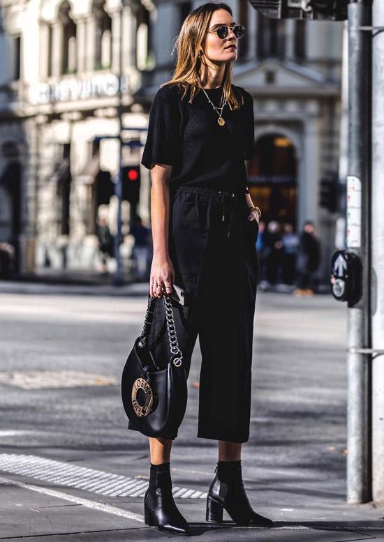 Девушка в укороченных брюках, черная футболка и ботильоны
