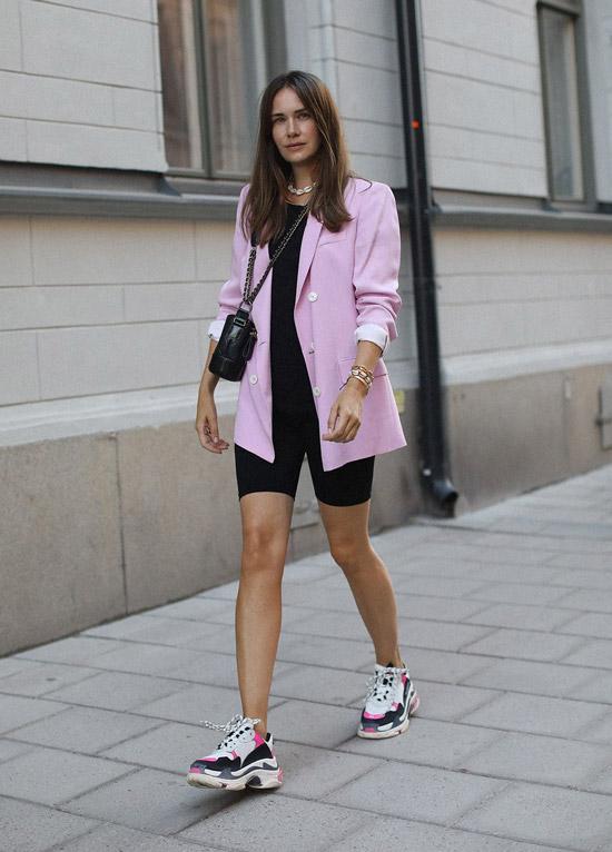 Девушка в велосипедных шортах, розовый блейзер и кроссовки