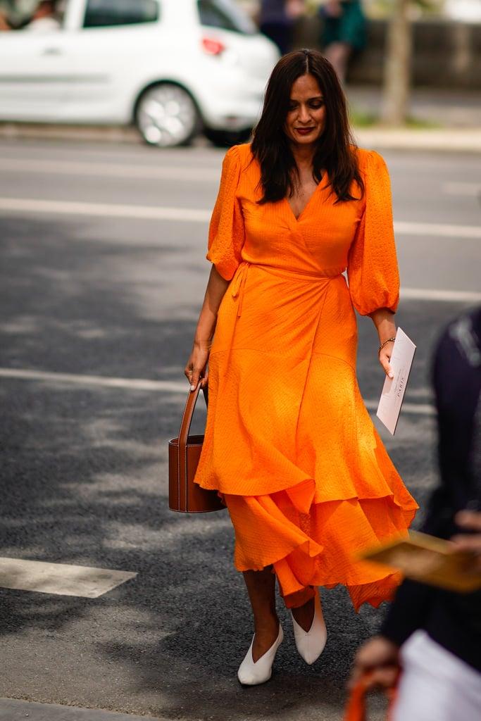Девушка в ярком оранжевом платье миди, белые туфли и сумка ведро