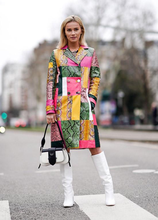 Девушка в ярком пальто в стиле печворк и белые сапоги