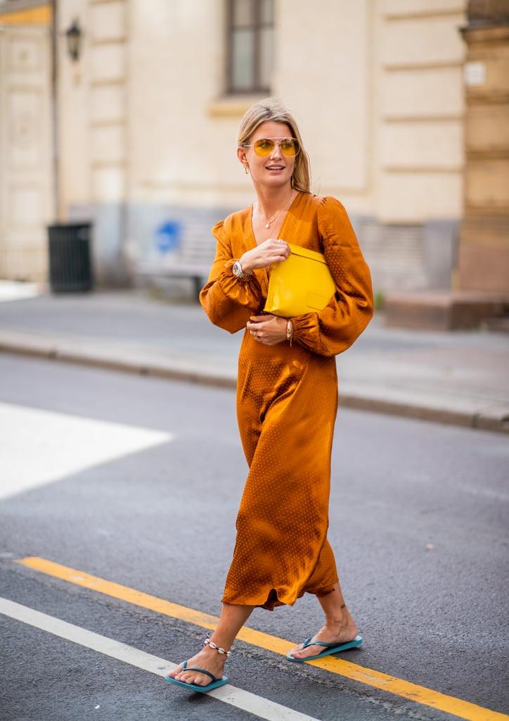 Девушка в ярком платье горчичного цвета, желтая сумка и сланцы