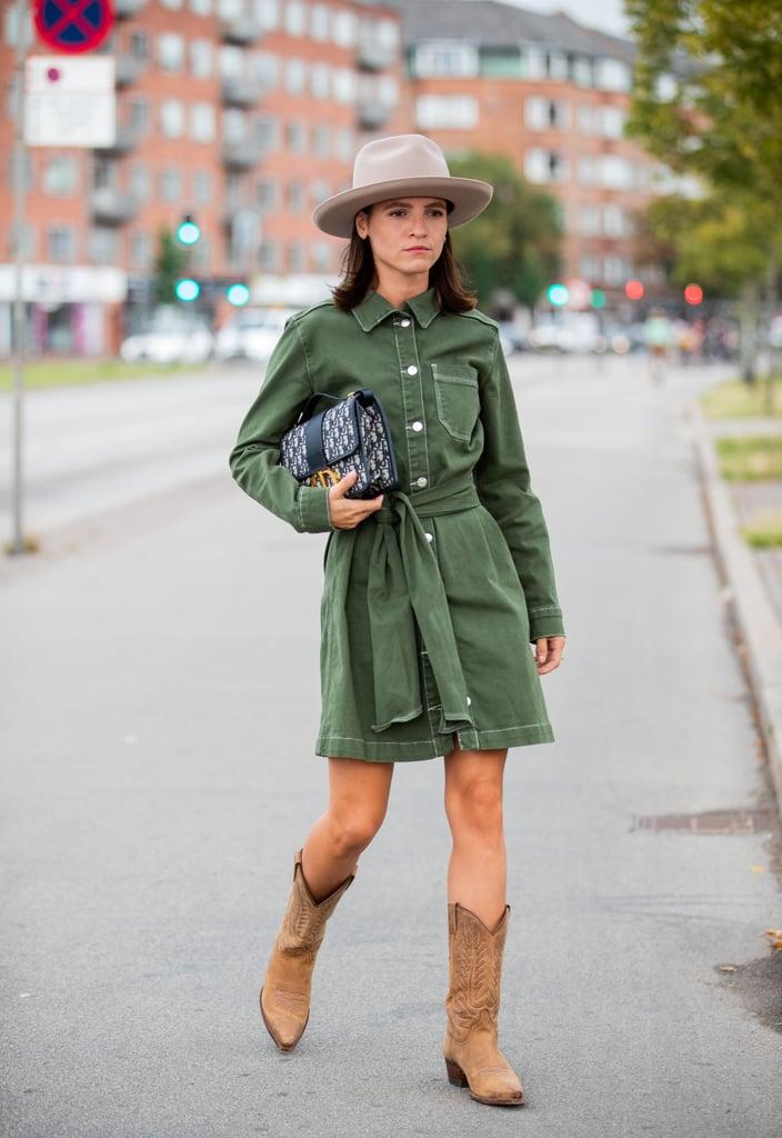 Девушка в зеленом коротком платье с поясом, ковбойсие сапоги и шляпа