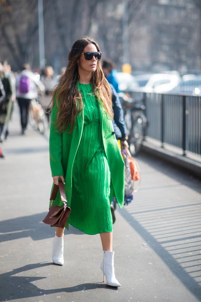 Девушка в зеленом платье миди, пальто и белые ботильоны