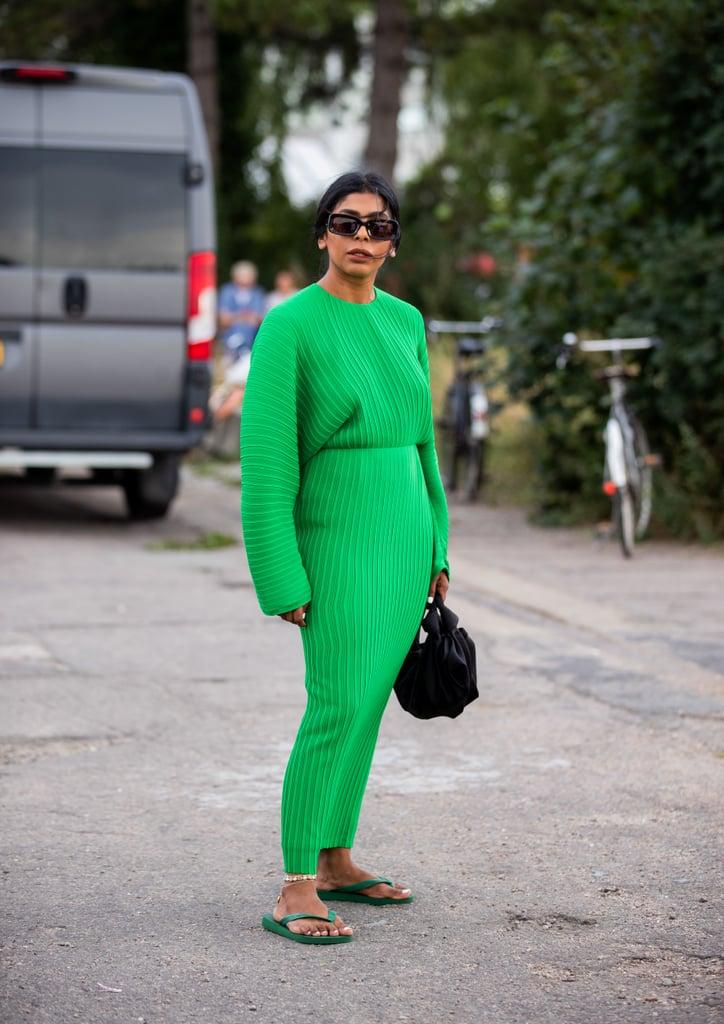 Девушка в зеленом трикотажном платье макси, черная сумка и сланцы