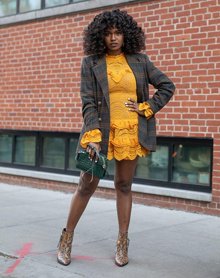 Девушка в желтом мини платье, блейзер в клетку и ботильоны из змеинной кожи