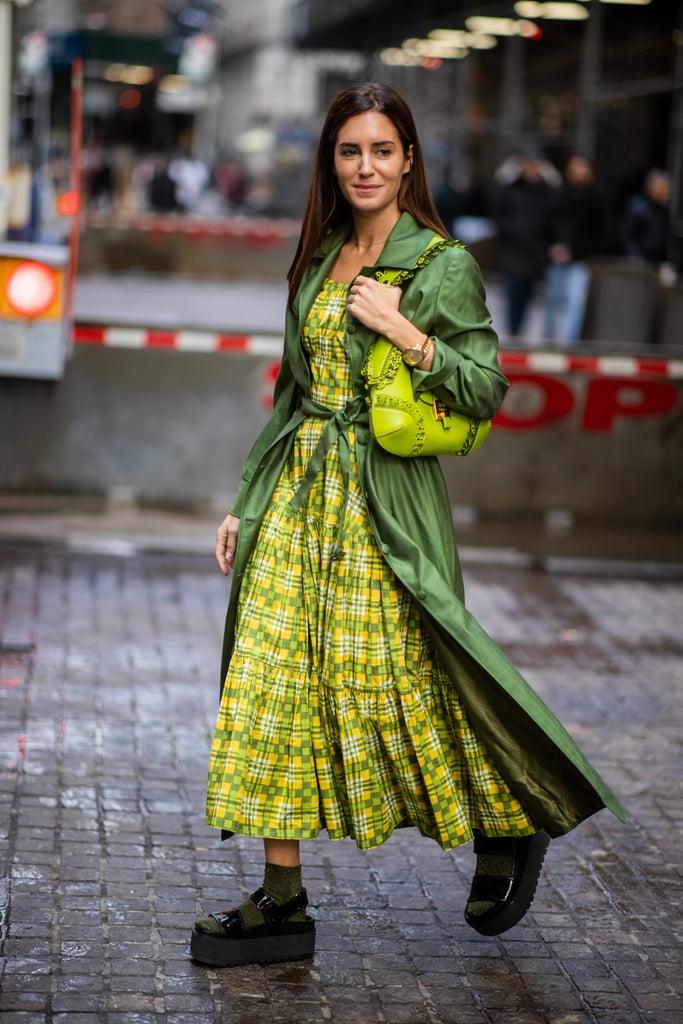 Девушка в желтом платье макси и зеленый плащ, черные сандалии на платформе