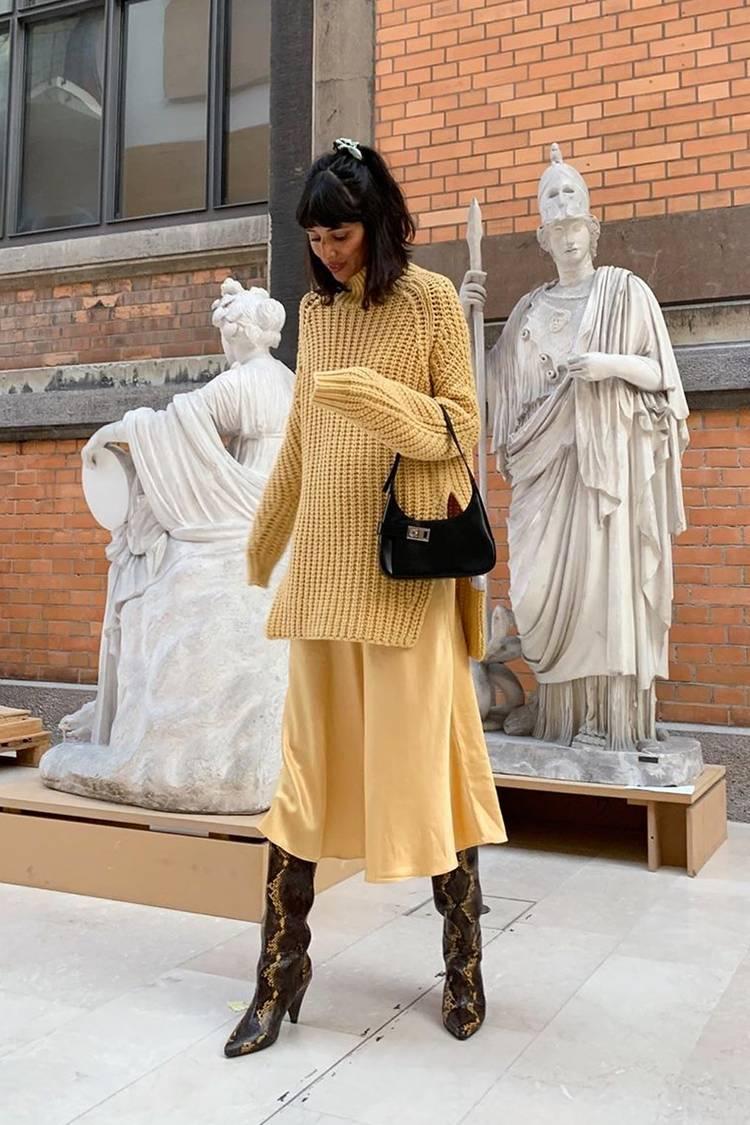 Девушка в желтой юбке миди, вязанный свитер оверсайз и сапоги из змеиной кожи