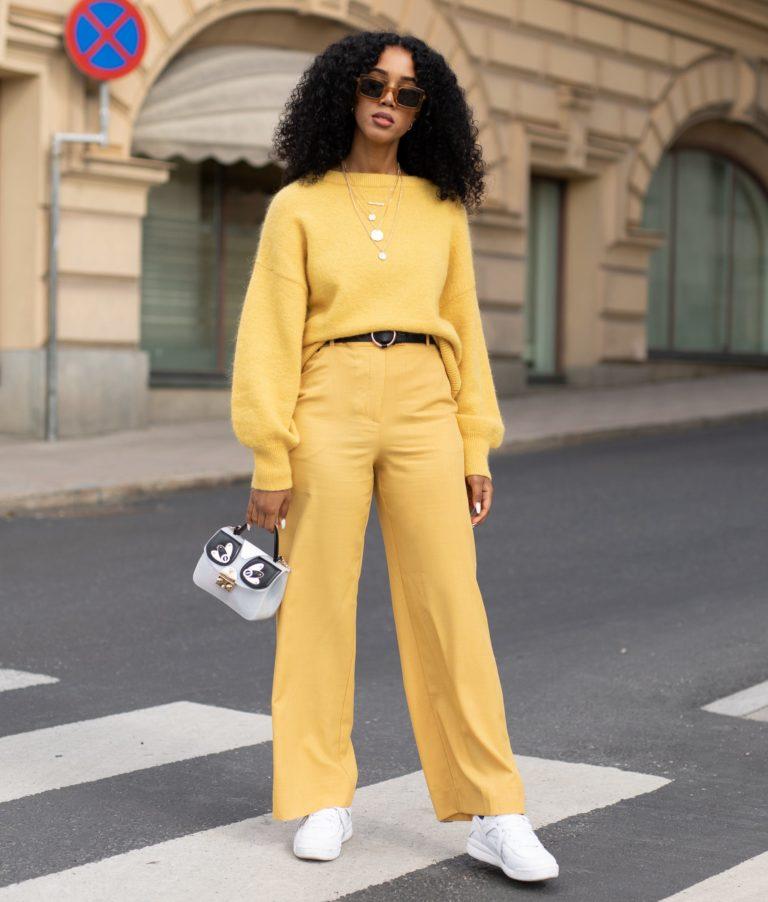 Девушка в желтых брюках с черным ремнем, джемпер и белые кеды