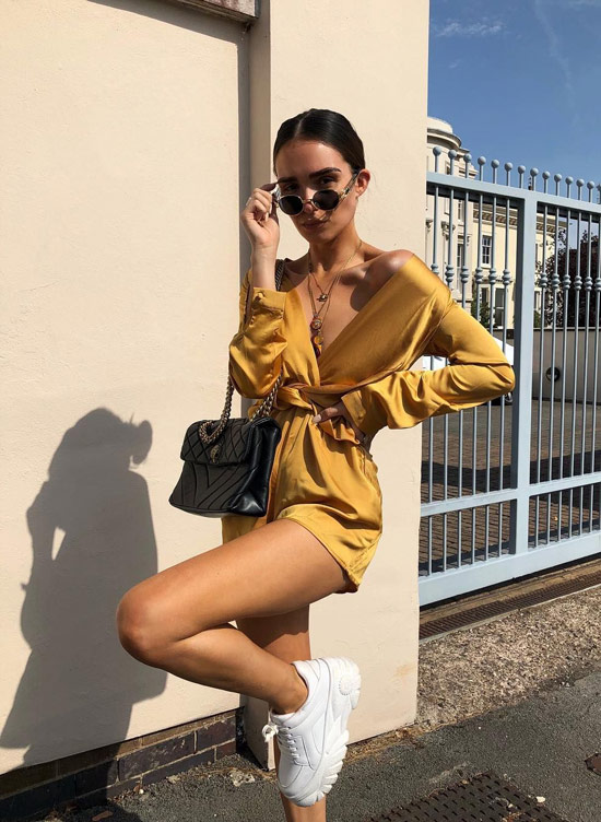 Девушка в золотом комбинезоне, черная сумочка и белые кроссовки