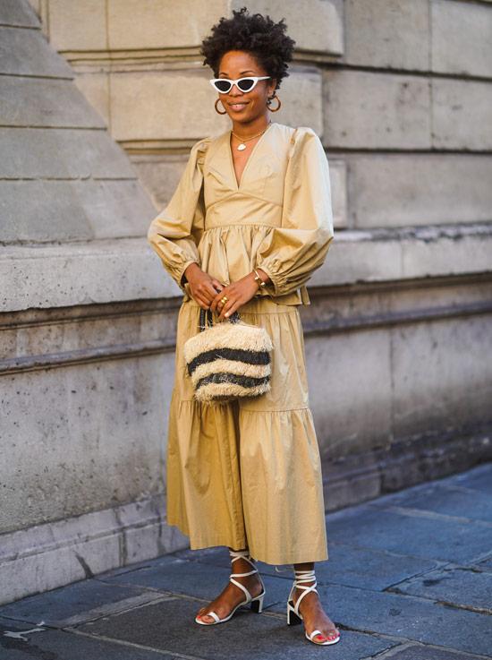 Девушка в комбинезоне песочного цвета и босоножках с ремешками