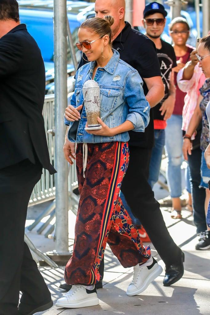 Jennifer Lopez в красных спортивных штанах, джинсовая куркта и белые кеды
