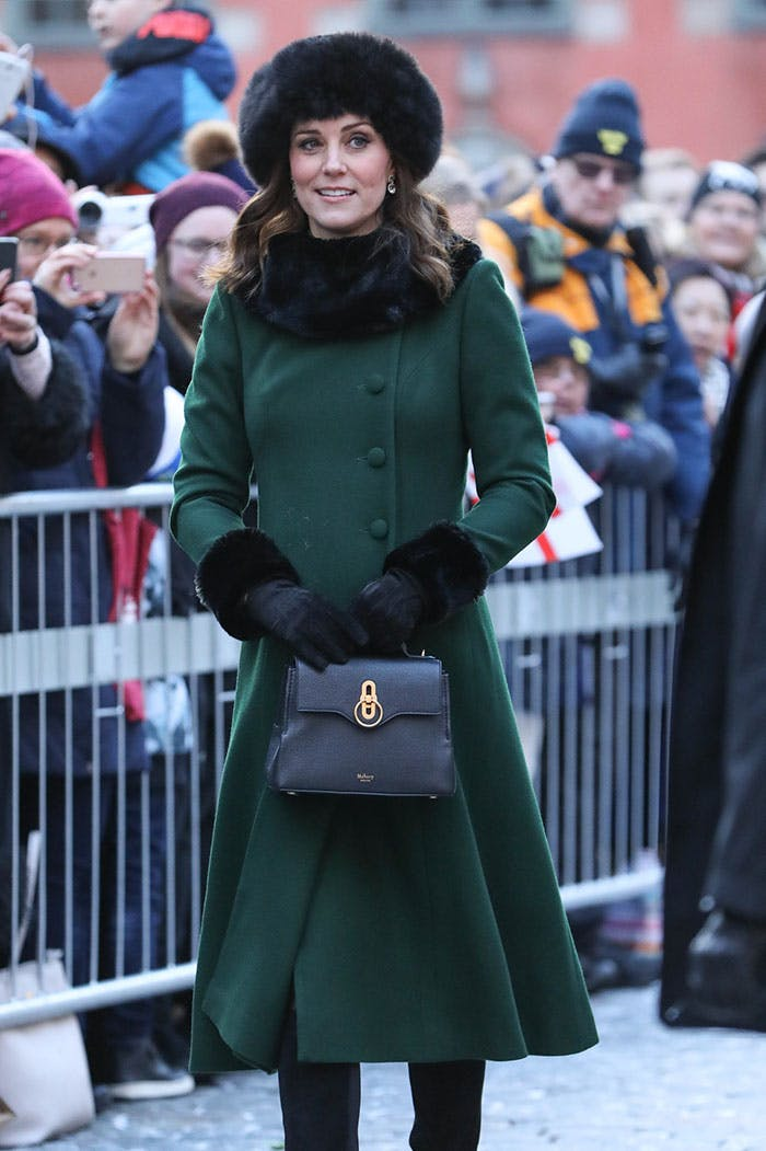 Кейт Миддлтон в зеленом приталенном пальто с меховой отделкой, меховая шапка и черная сумочка