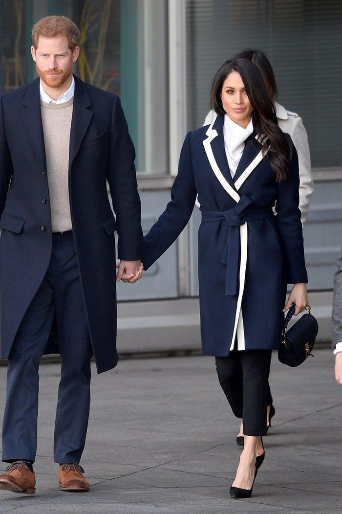 Меган Маркл в темно-синем пальто с белой отделкой и поясом, черные брюки, туфли на шпильке