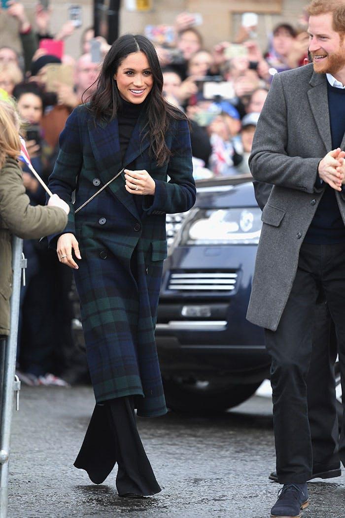 Меган Маркл в темном пальто оверсайз в клетку и черных брюках клеш
