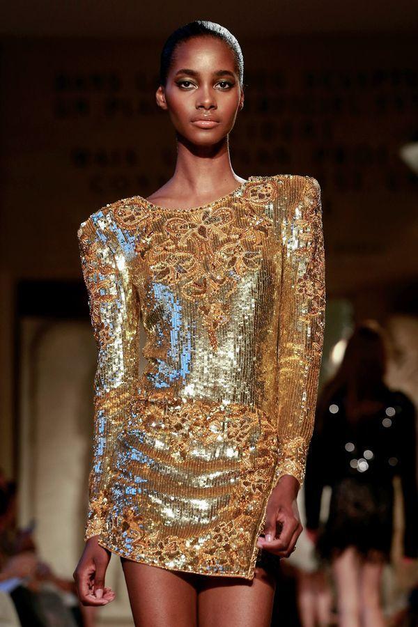 Модель в золотом мини платье с длинными рукавами