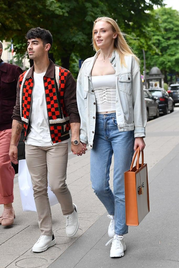 Sophie Turner в синих джинсах, белая джинсовая куртка и кроссовки