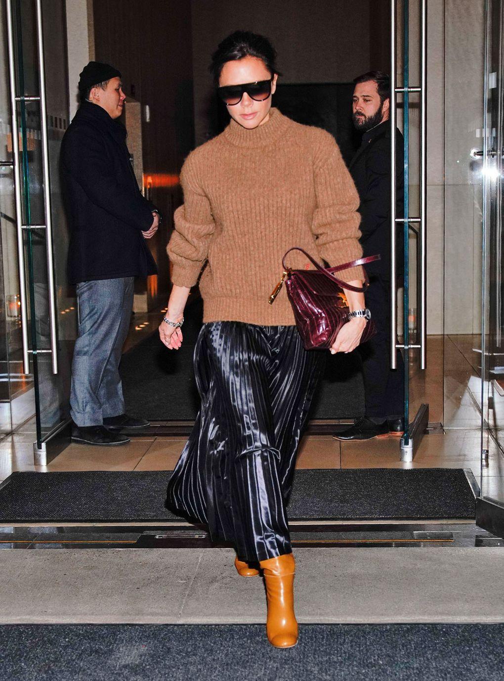 Виктория Бекхэм в черной плиссированной юбкке, оричневый свитер и оранжевые сапоги