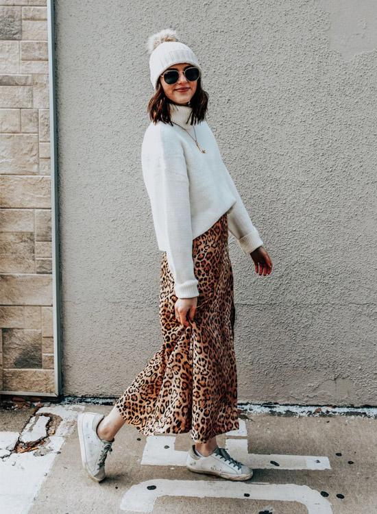 девушка в леопардовой юбке, белом свите, шапке и кедах