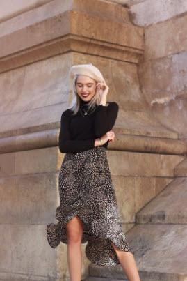 девушка в леопардовой юбке, черной кофте и бежевом берете