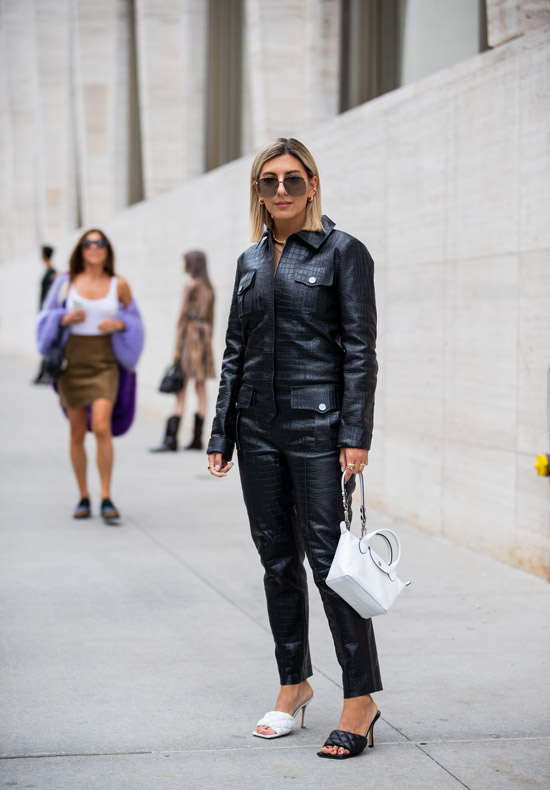 Aylin Koenig в черном кожаном комбинезоне, белая сумка и босоножки разного цвета