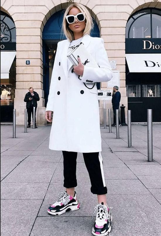 Девушка в белом пальто, черные брюки и кроссовки