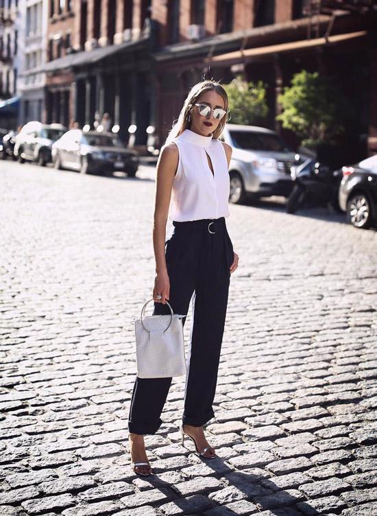 Девушка в белом топе, черные широкие брюки и серебристые босоножки