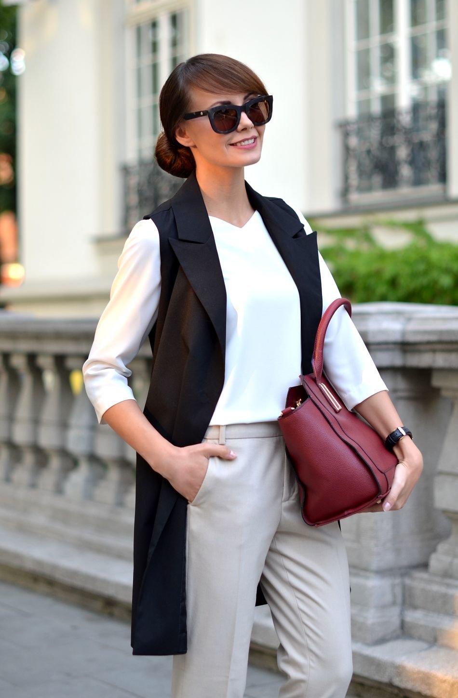 Девушка в белой блузке, бежевые брюки и черный удлиненный жилет