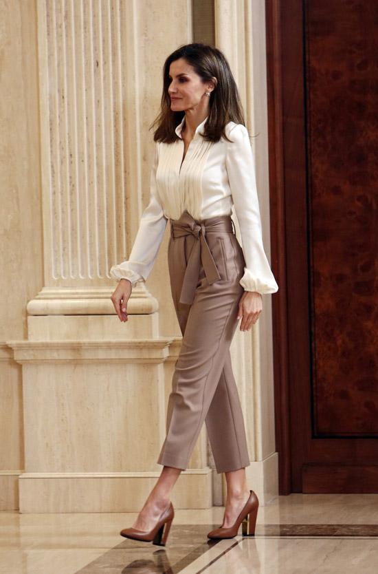 Девушка в белой блузке с длинными рукавами и укороченные бежевые брюки