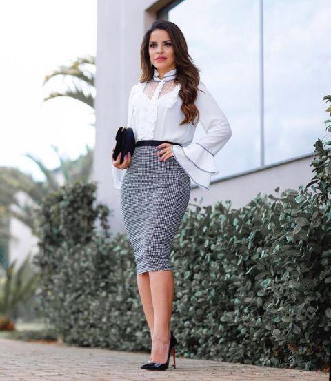 Девушка в белой блузке с рукавами клеш, серая юбка карандаш и черные туфли на шпильке