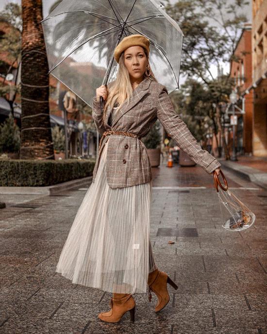 Девушка в белой плиссированной юбке, бежевый блейзер в клетку с поясом, прозрачный зонт
