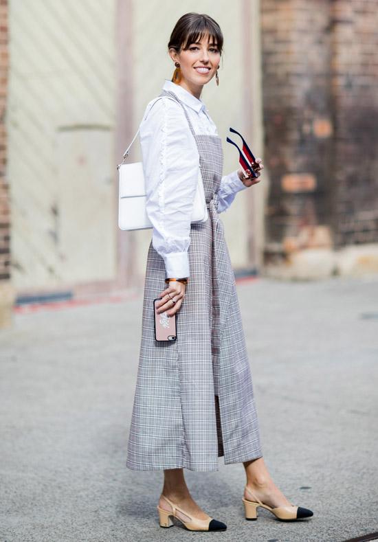 Девушка в белой рубашке, сарафан в клетку и туфли на низком каблуке