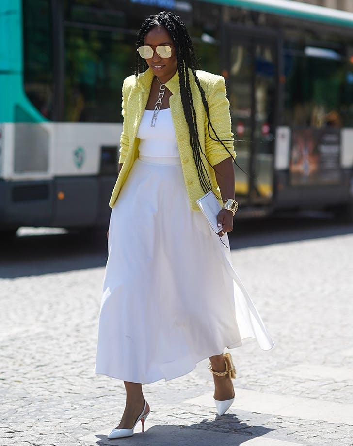 Девушка в белой свободной юбке, топ и желтый жакет