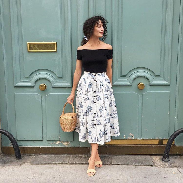 Девушка в белой юбке миди, черный топ и соломенная сумка