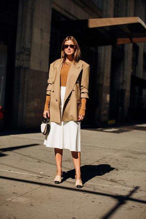 Девушка в белой юбке, пиджаке и туфлях с цветным носком