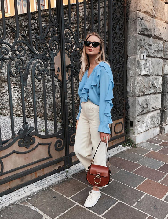 Девушка в белых брюках, голубая блузка с рюшами и белые кеды
