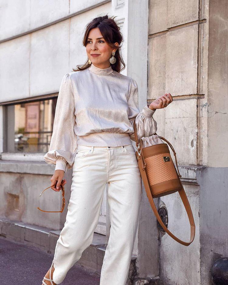 Девушка в белых джинсах, шелковая блузка с пышными рукавами и коричневая сумка ведро