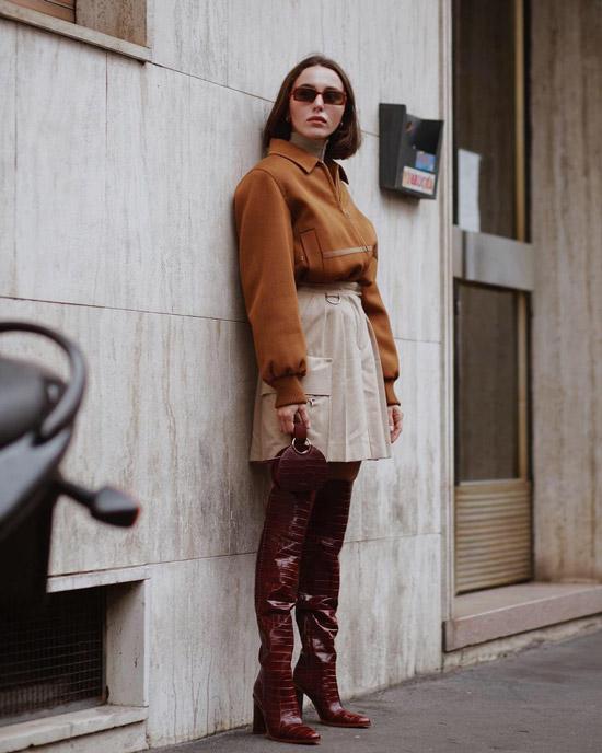 Девушка в бежевой мини юбке, теплая кофта и лакированные ботфорты на каблуке