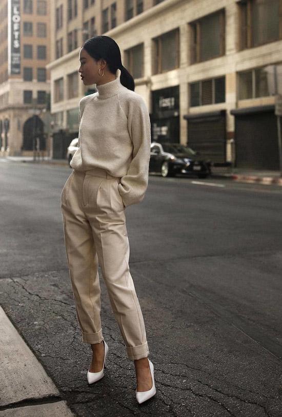 Девушка в бежевых брюках, свитер и белые туфли