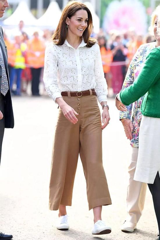 Девушка в бежевых свободных брюках с поясом, белая рубашка и кеды