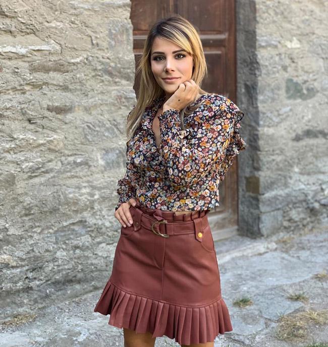 Девушка в блузке с цветочным принтом и коричневая юбка из кожи