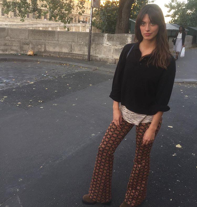 Девушка в брюках клеш, черный свитер и ботинки