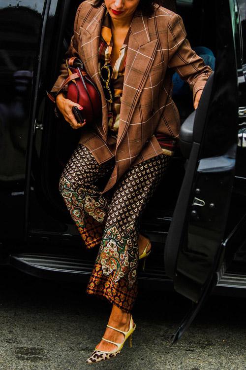 Девушка в брюках с принтом, пиджаке в клетку и туфлях с леопардом