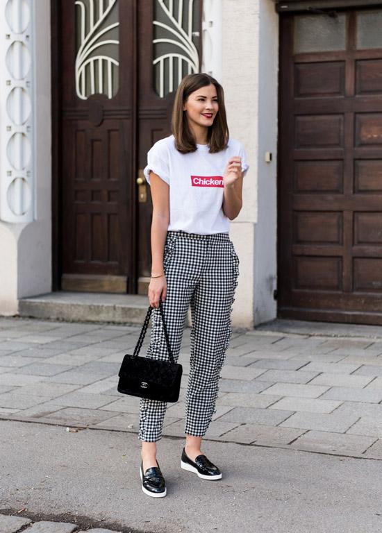 Девушка в брюках в клетку, белая футболка и черные слипоны